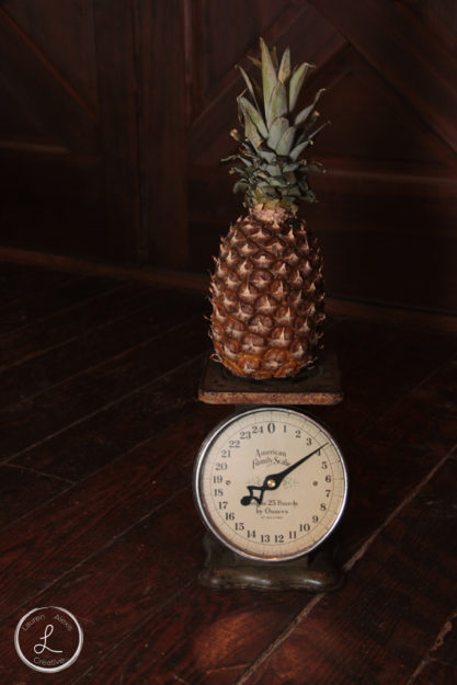 farm fresh fruit, fruit on a scale, pineapple, pineapple being weighed, balancing light on objects